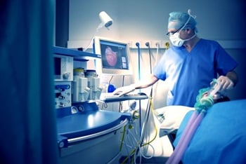 A doctor using ventilators to treat patient in ICU